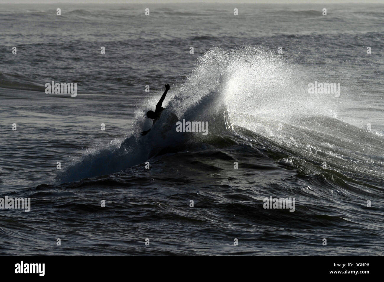 Surfer Lloyd Cole executes a tricky turn at the Sand Bar almost disappearing in a cloud of spray - Stock Image