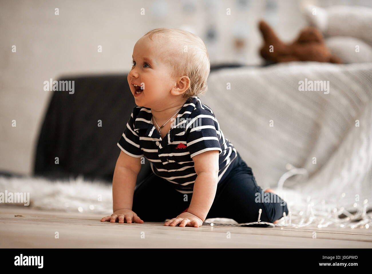 Small baby crawling on floor and laughs merrily. He is very pleased. - Stock Image