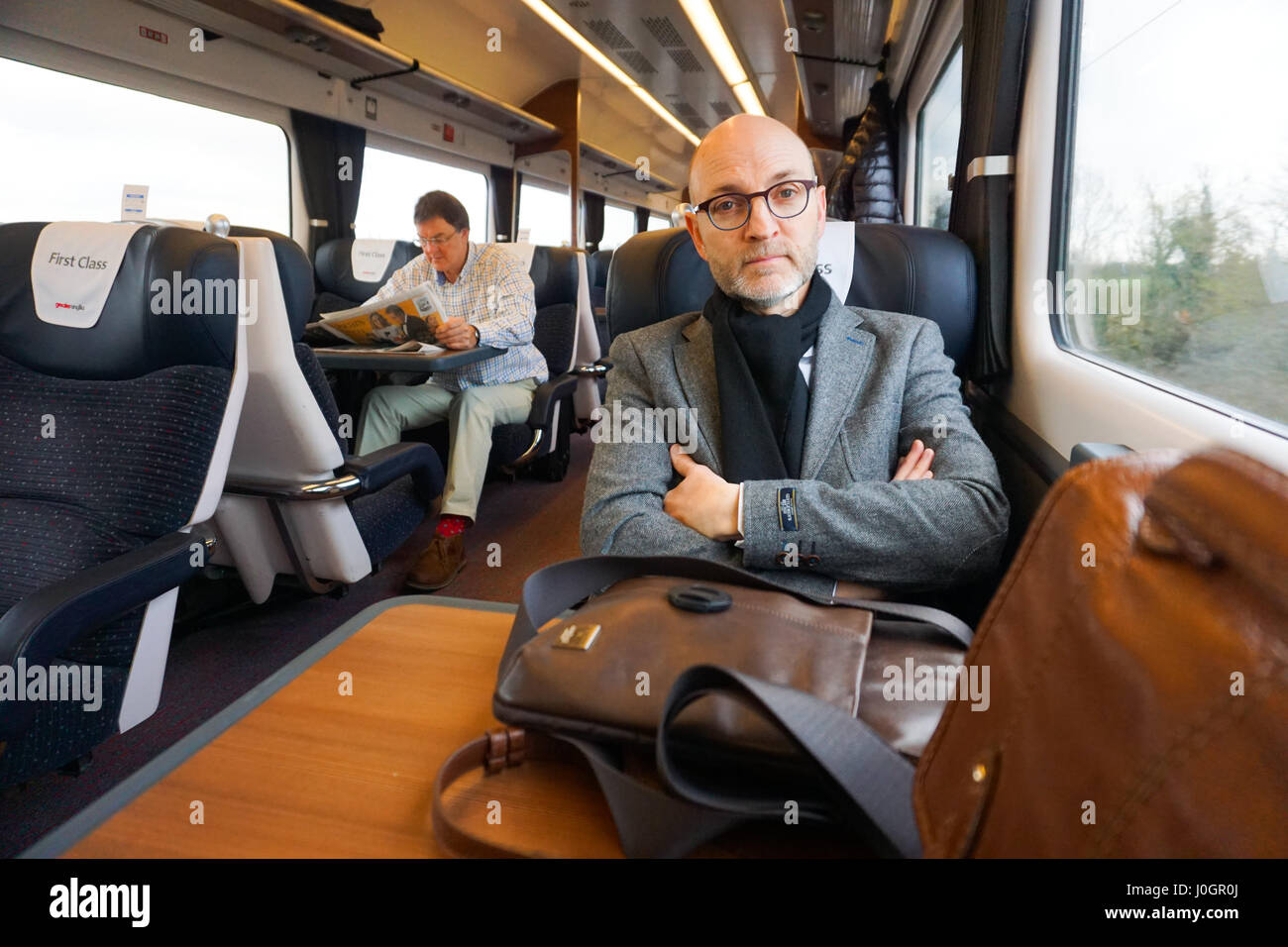 A middle aged male figure sitting on the train wearing jacket and glasses in first class carriage - Stock Image