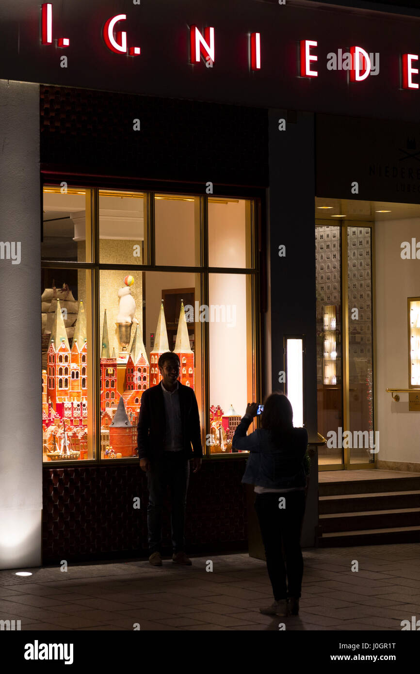 Tourists looking at shop window display at J.G. Niederegger famous marzipan candy shop in Lubeck, Germany - Stock Image