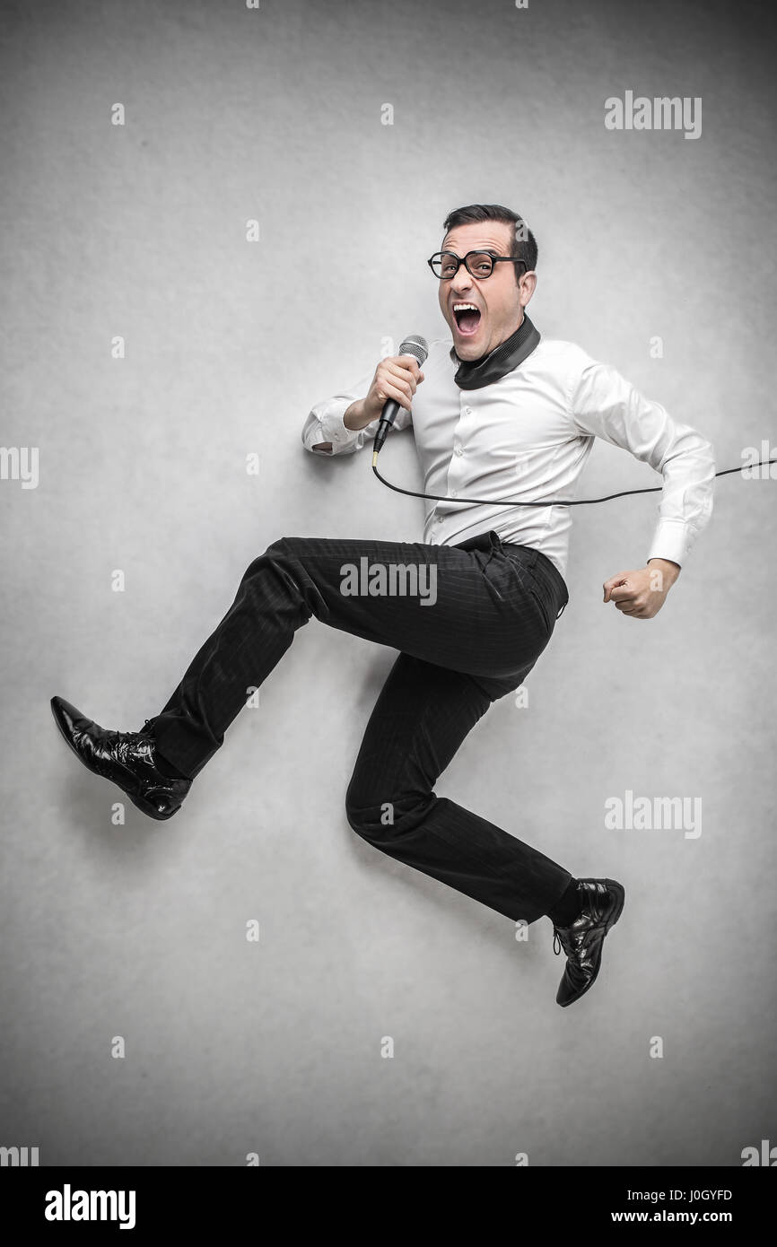 Businessman running with microphone - Stock Image