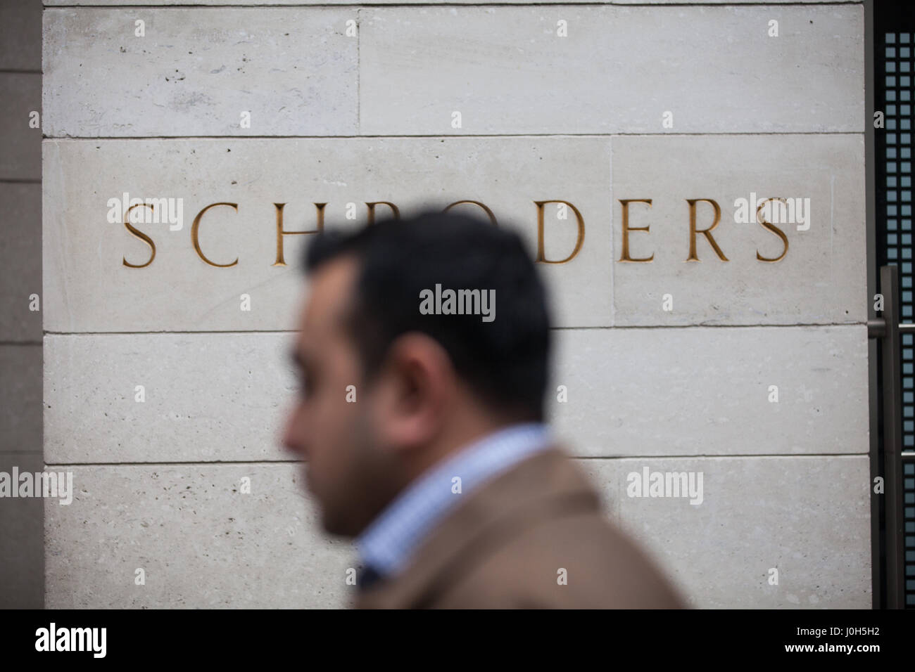 London, UK. 13th April, 2017. A man walks past a sign outside the offices of Schroders in the City of London. Credit: - Stock Image