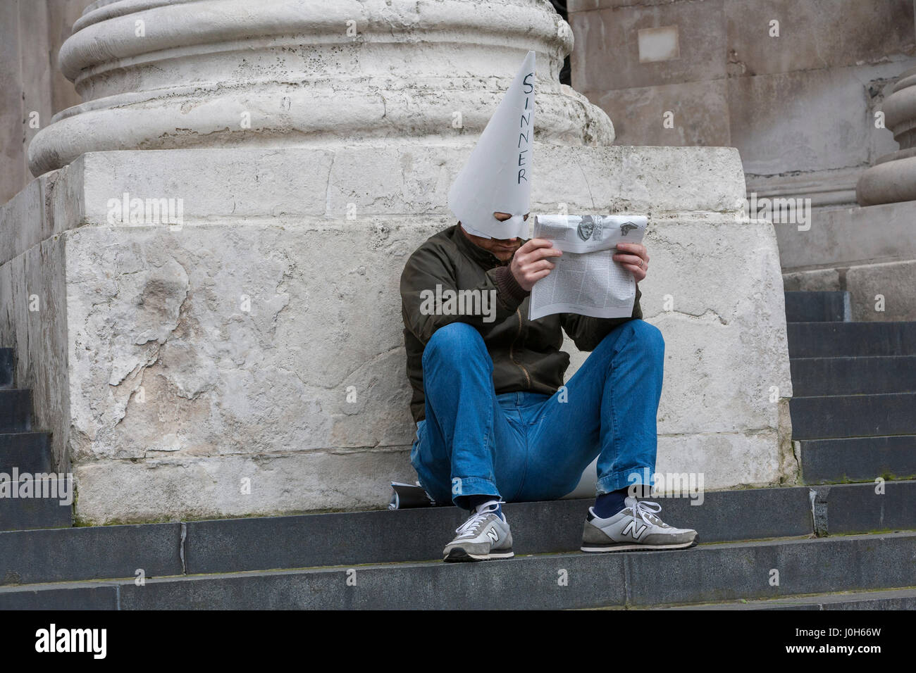 London, UK. 13th Apr, 2017. A solitary man sits on the steps of St. Paul's Cathedral reading a newspaper wearing - Stock Image