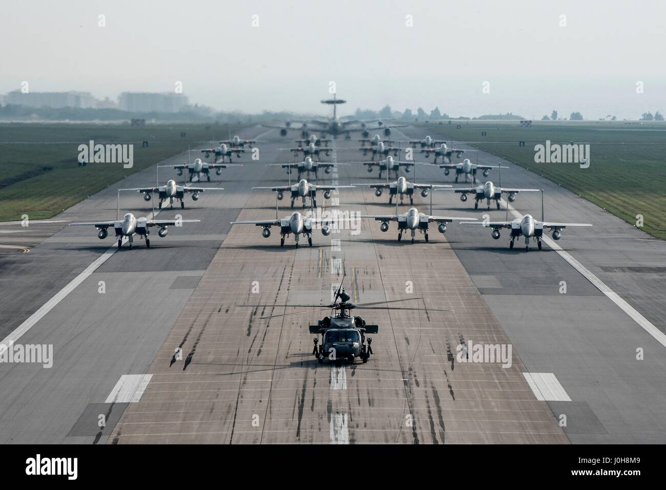 U.S. Air Force 18th Wing taxis down the runway with combat ready HH-60 Pave Hawks, F-15 Eagles, E-3 Sentries and - Stock Image