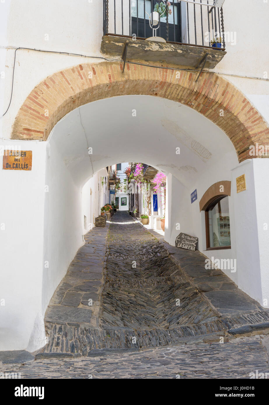 An arch passageway through a whitewashed building along Carrer des Call known for its herringbone rastell cobble - Stock Image