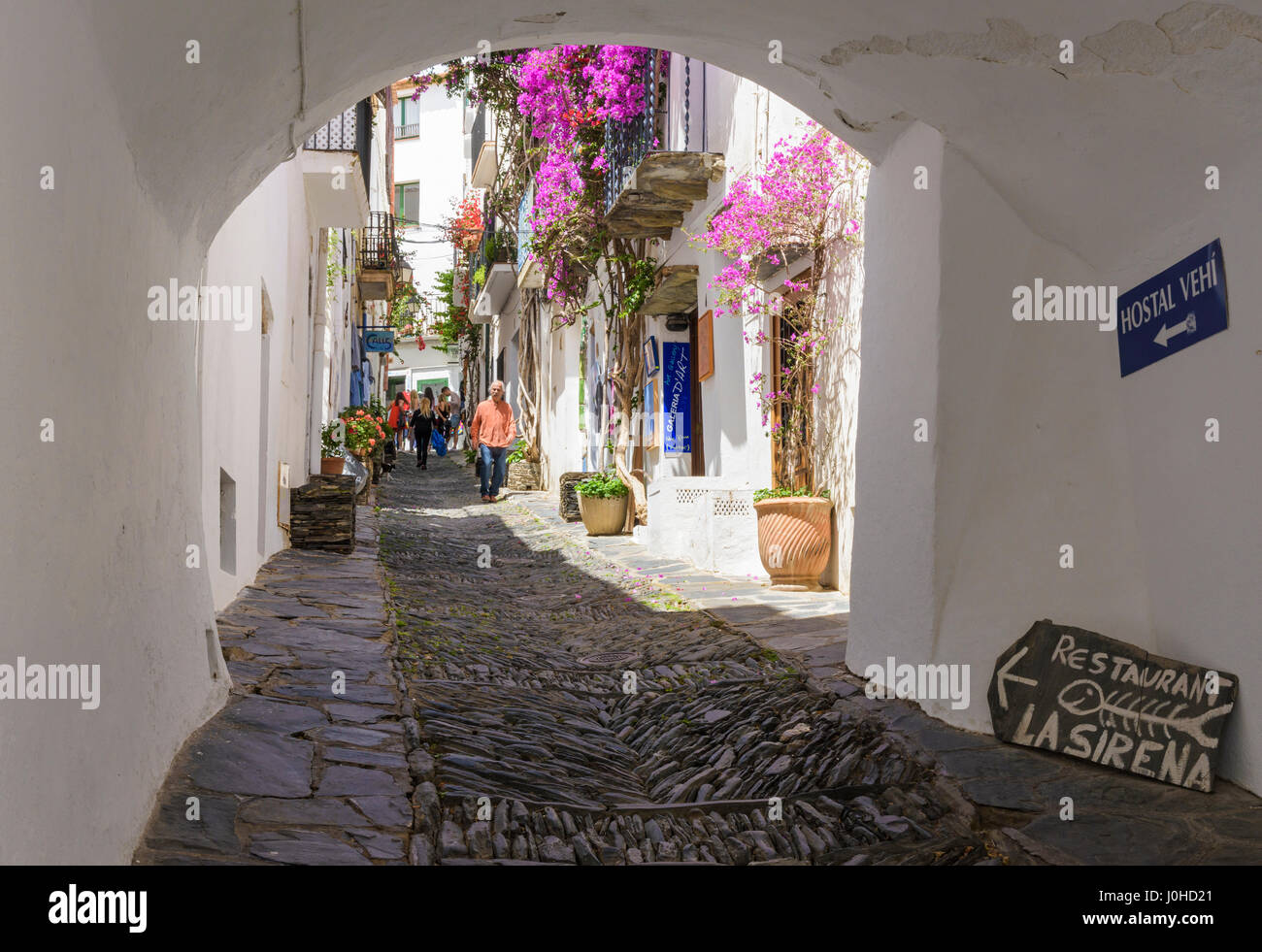 An arch passageway along pretty Carrer des Call known for its herringbone rastell cobble pavement, Cadaques, Catalonia, - Stock Image