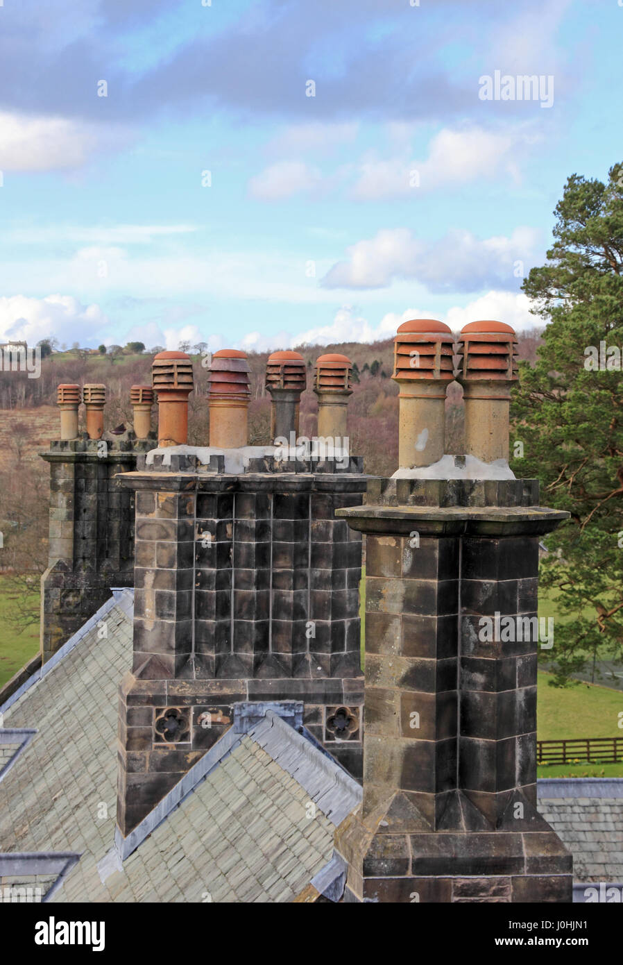 Row of chimney pots on top of historic house - Stock Image