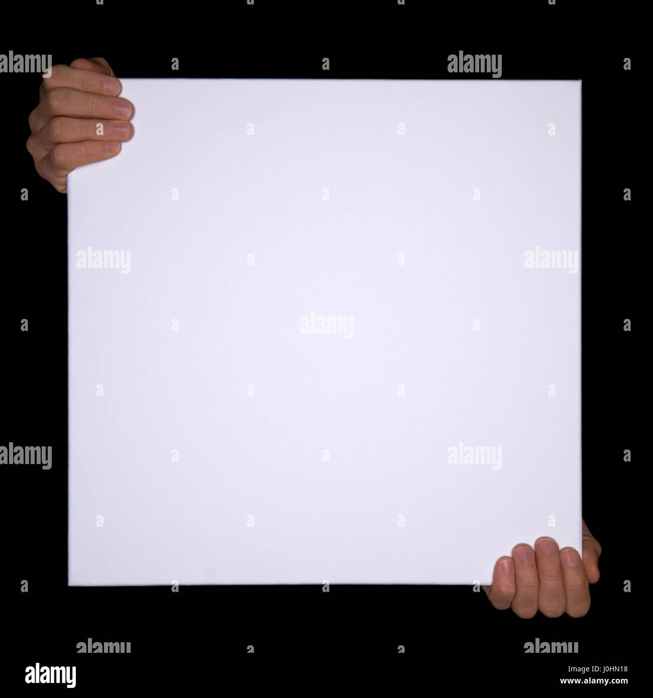 Isolated hands holding a empty canvas on black Background with copyspace. - Stock Image