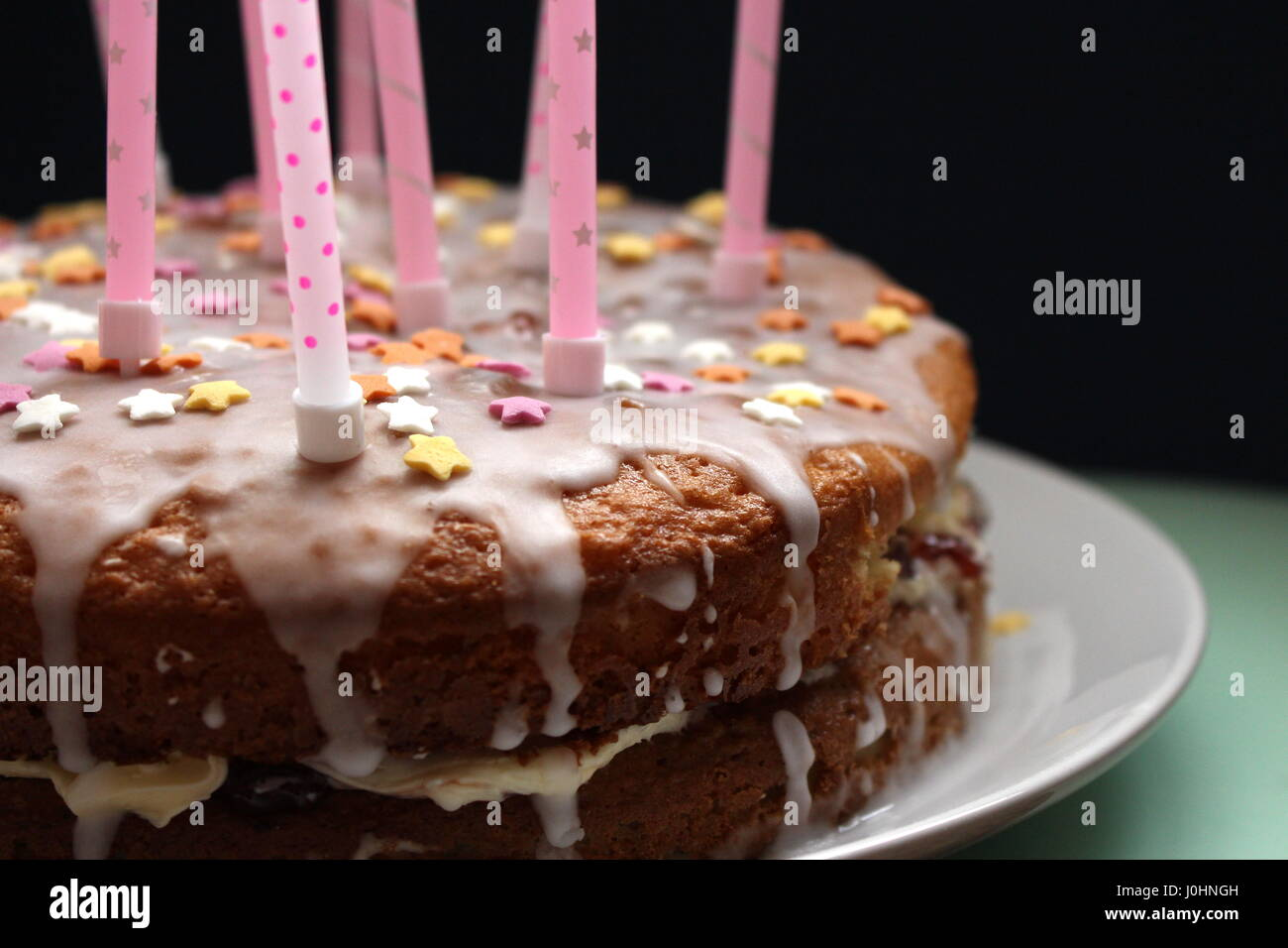 Birthday victoria sponge cake with runny icing, and pink candles, with sugar star decorations, against a black background - Stock Image