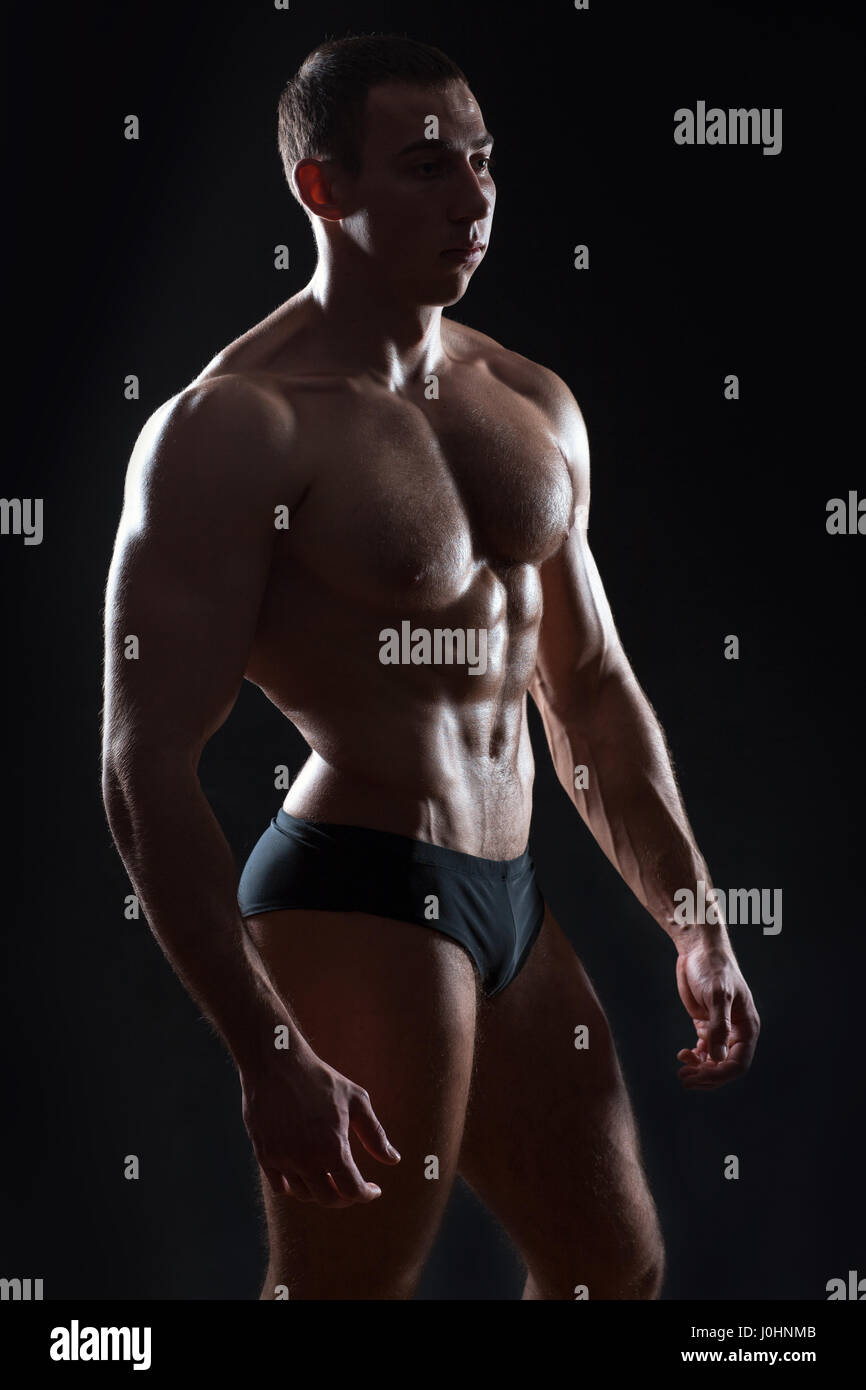 Calm bodybuilder standing on a dark background it shine large muscles of the body. - Stock Image