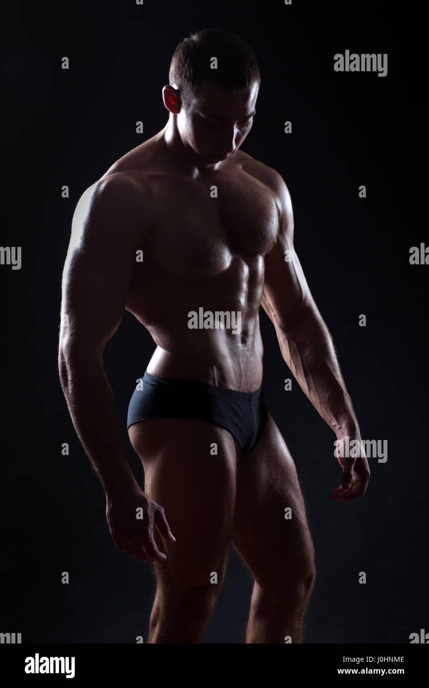 Beautiful bodybuilder figure in a dark vein underlined muscle. On a black background. - Stock Image