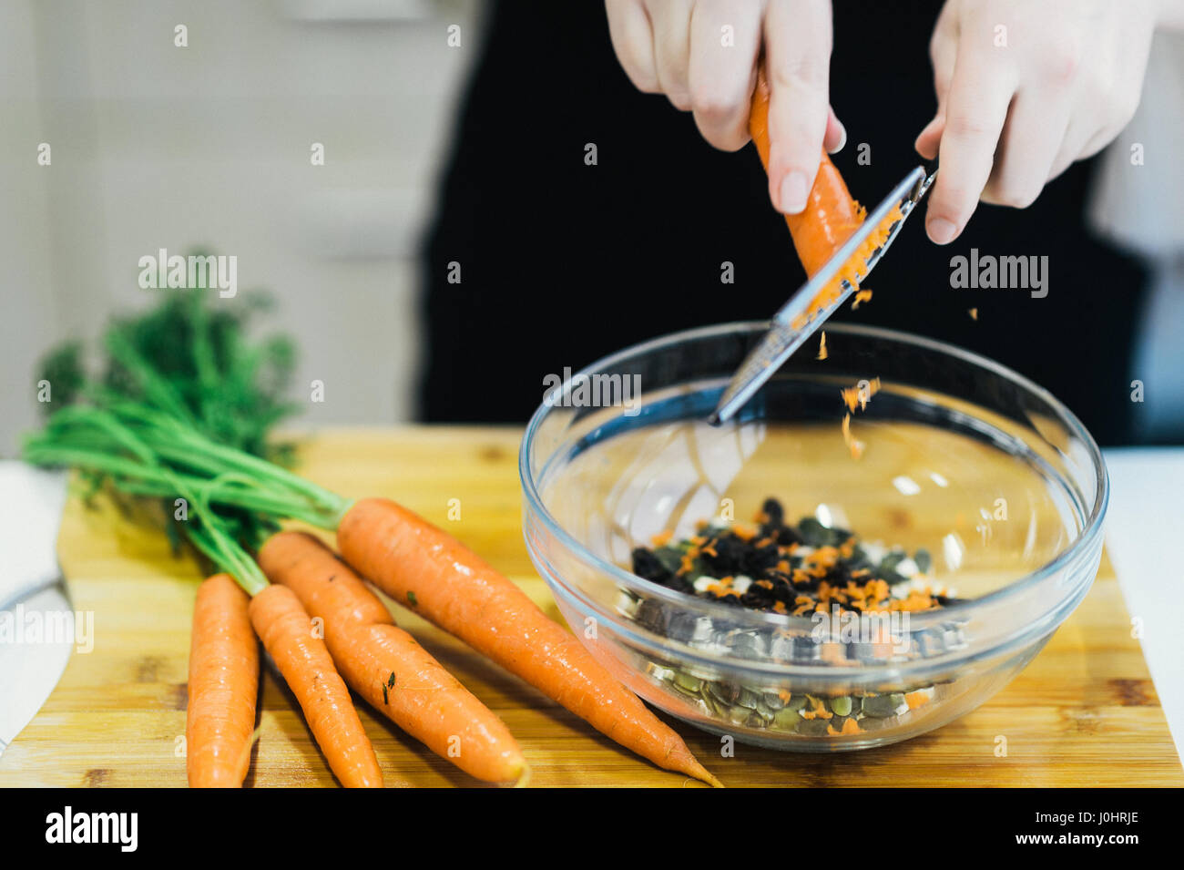 A Cook Grating Carrot to bake a Carrot Cake - Stock Image
