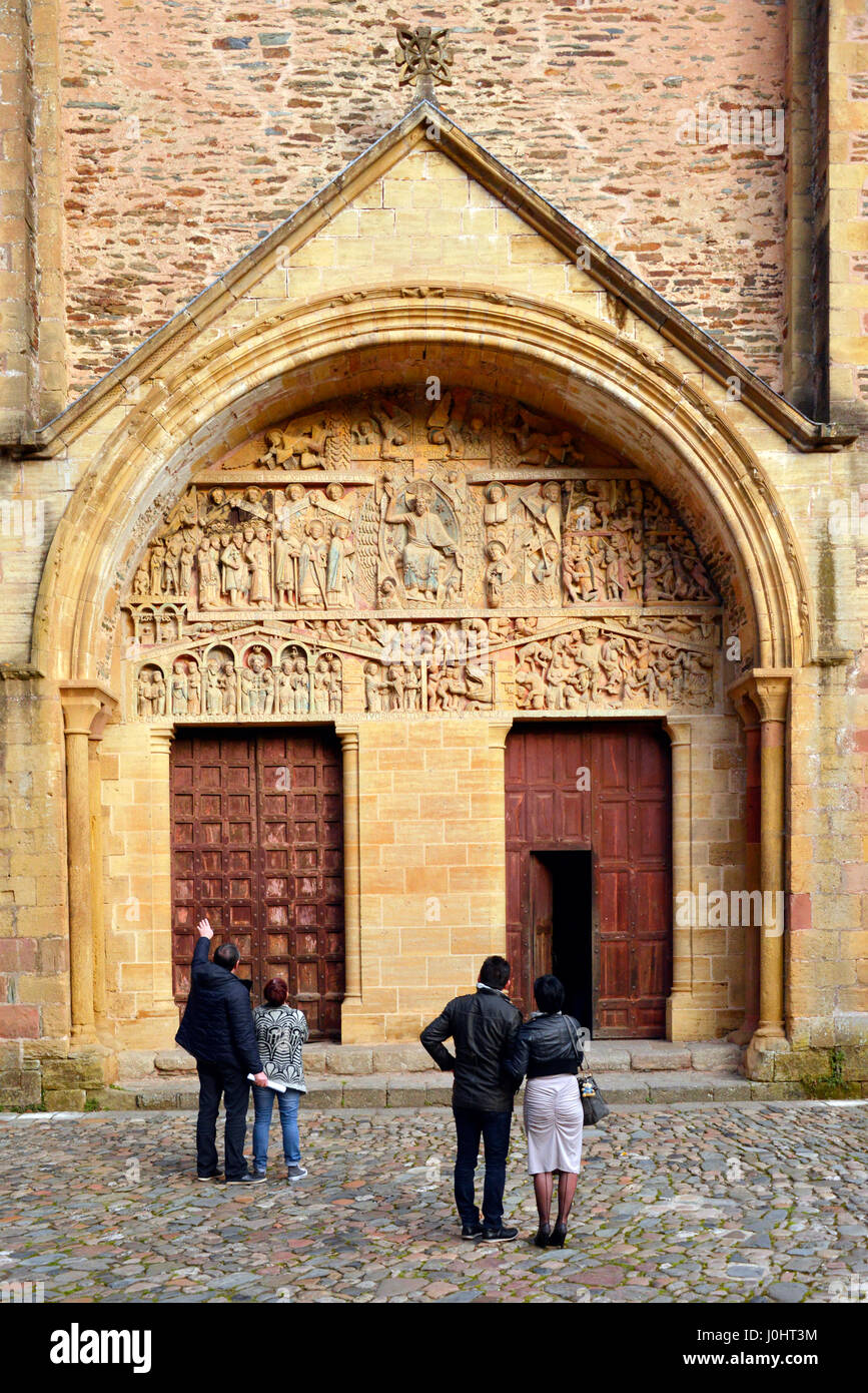 Tourists viewing the doors on the western facade of the 11th century Saint Foy Abbey church in Conques, Occitanie, - Stock Image