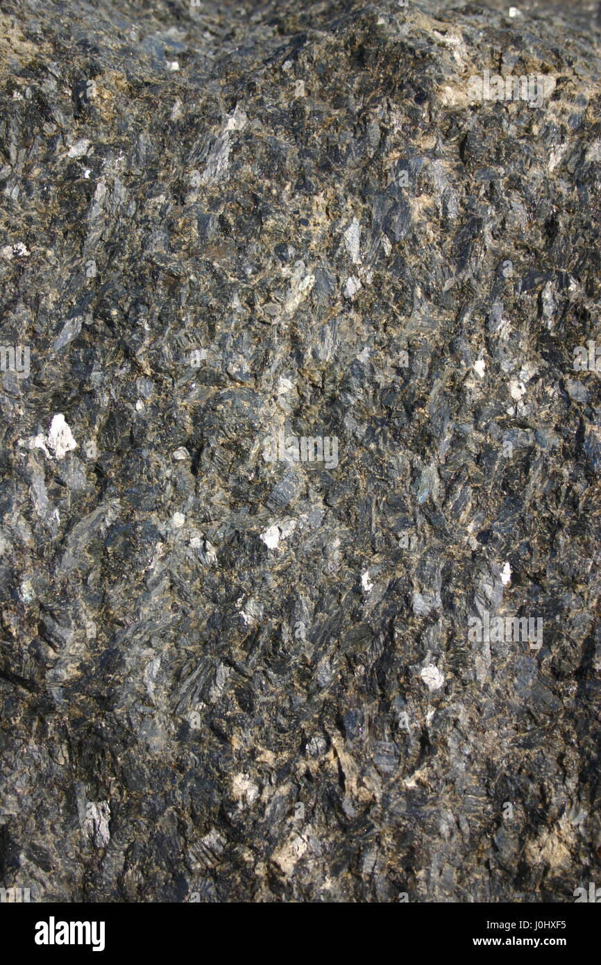A dark grungy rock surface  as a background. - Stock Image