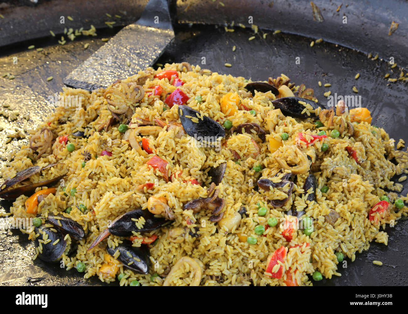 large pan of Spanish restaurant with tasty paella with yellow rice and mussels and seafood Stock Photo