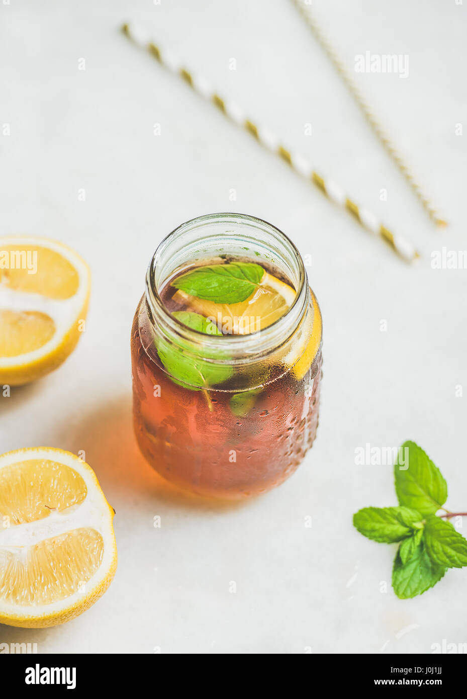 Summer cold Iced tea with lemon slices and fresh herbs - Stock Image