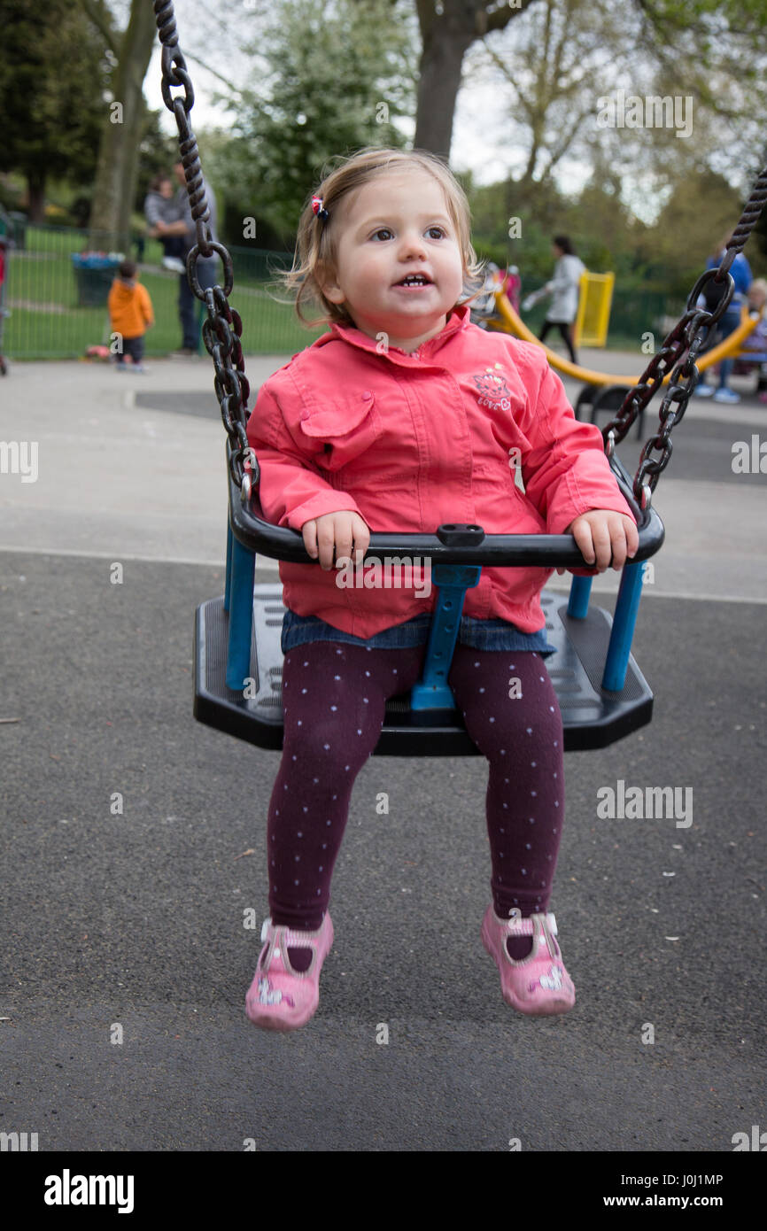 Girl toddler of 16 months in a public park playground - Stock Image