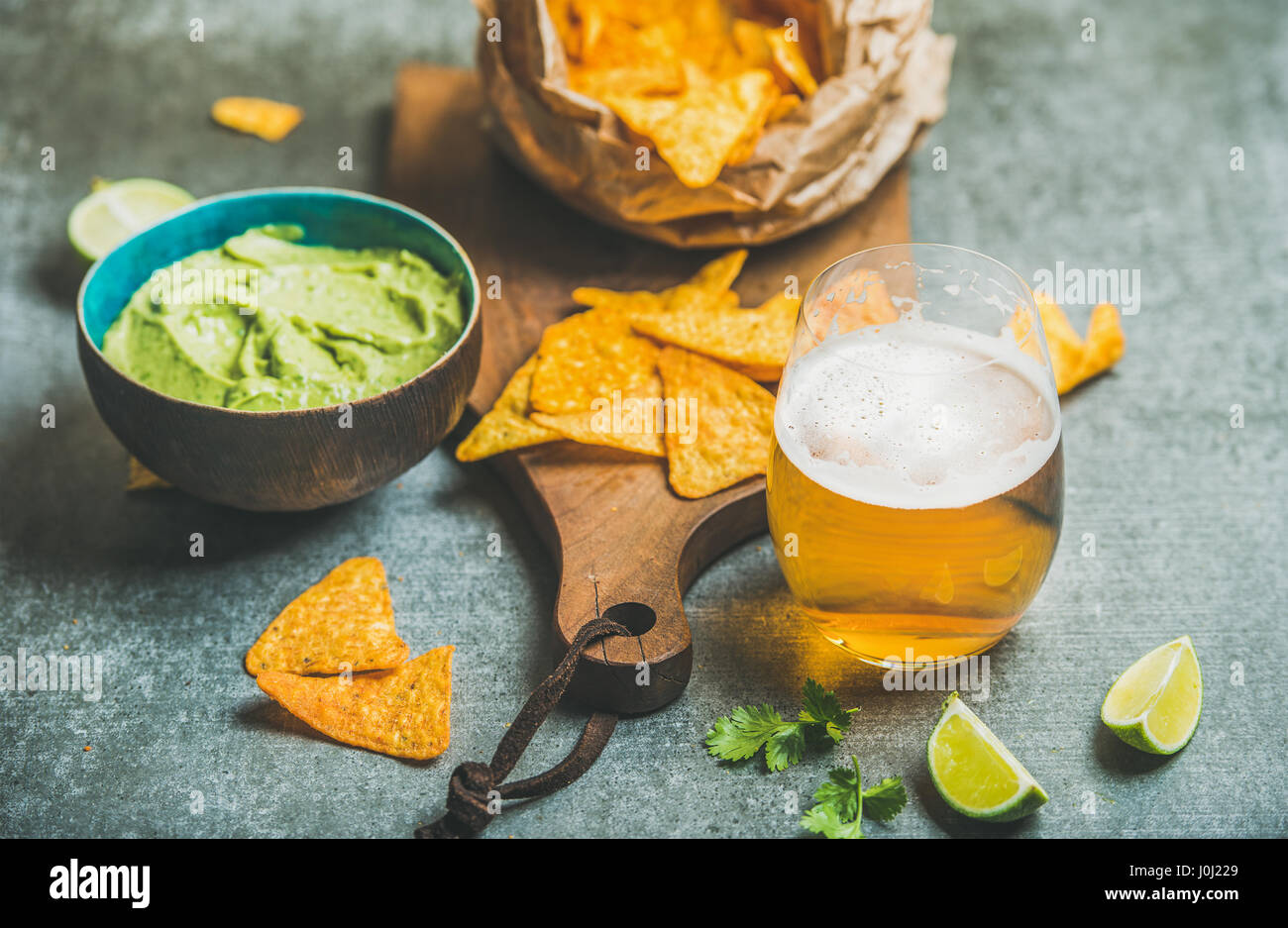 Mexican corn chips, fresh lime, guacamole sauce and wheat beer - Stock Image