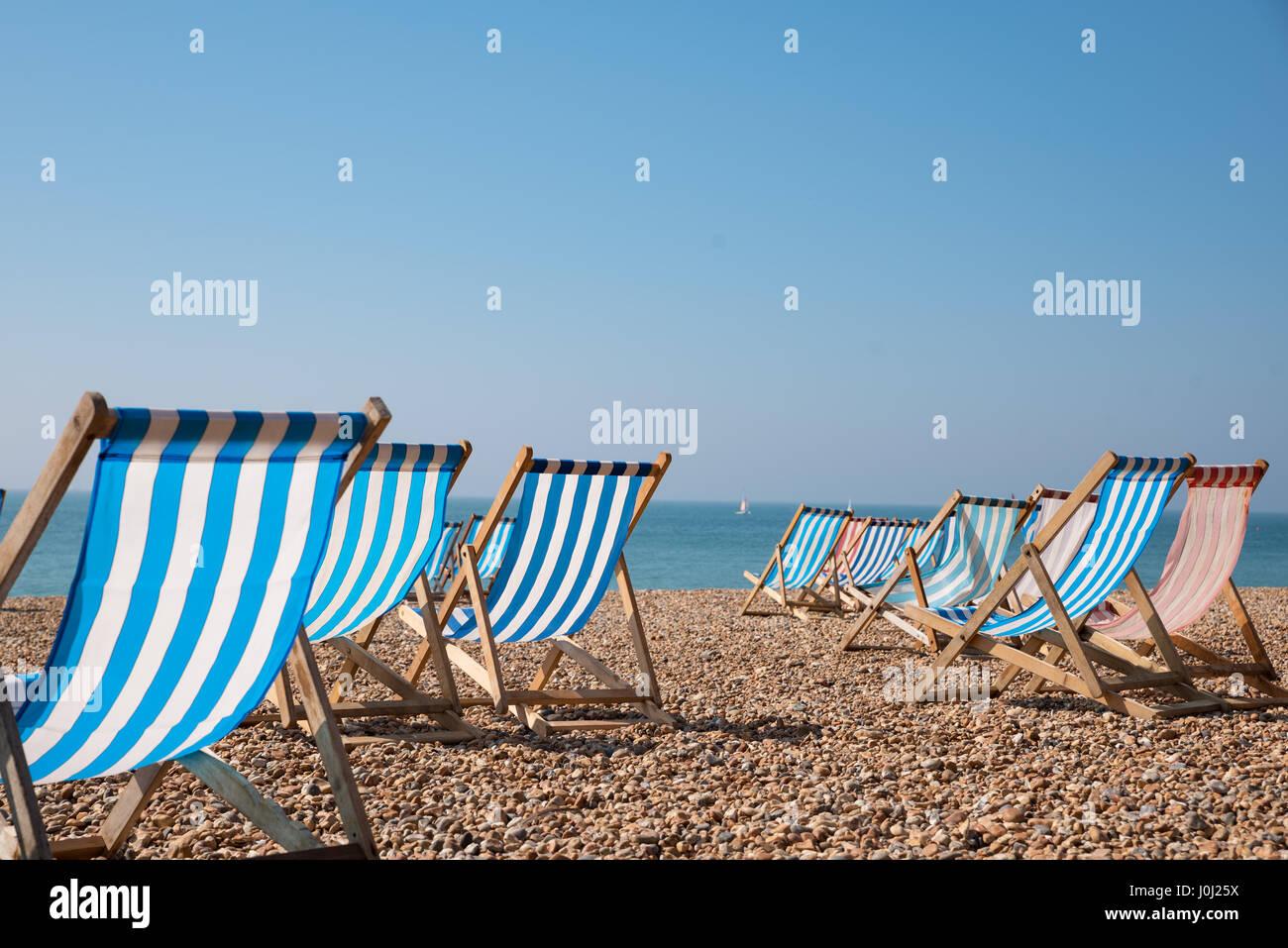 Empty traditional striped deckchairs on Brighton beach, England, UK - Stock Image