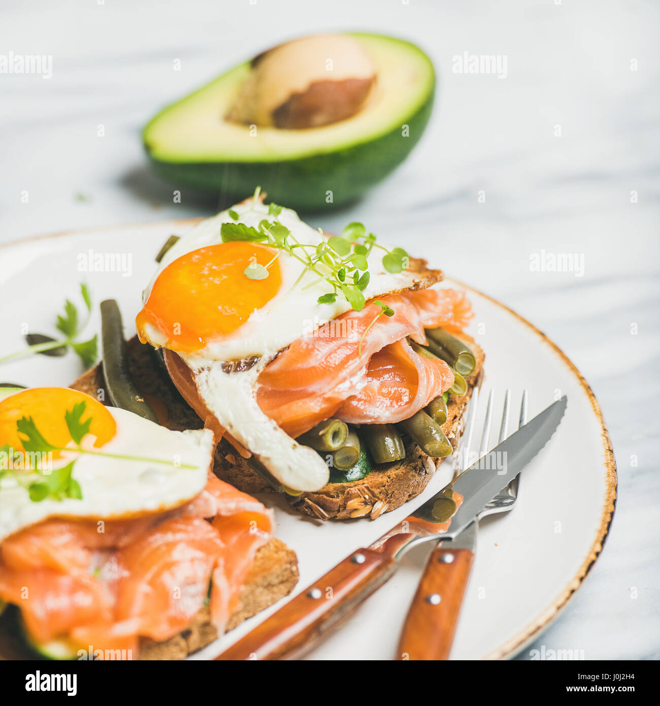Salmon, avocado, fried egg, beans and sprouts sandwiches, square crop - Stock Image