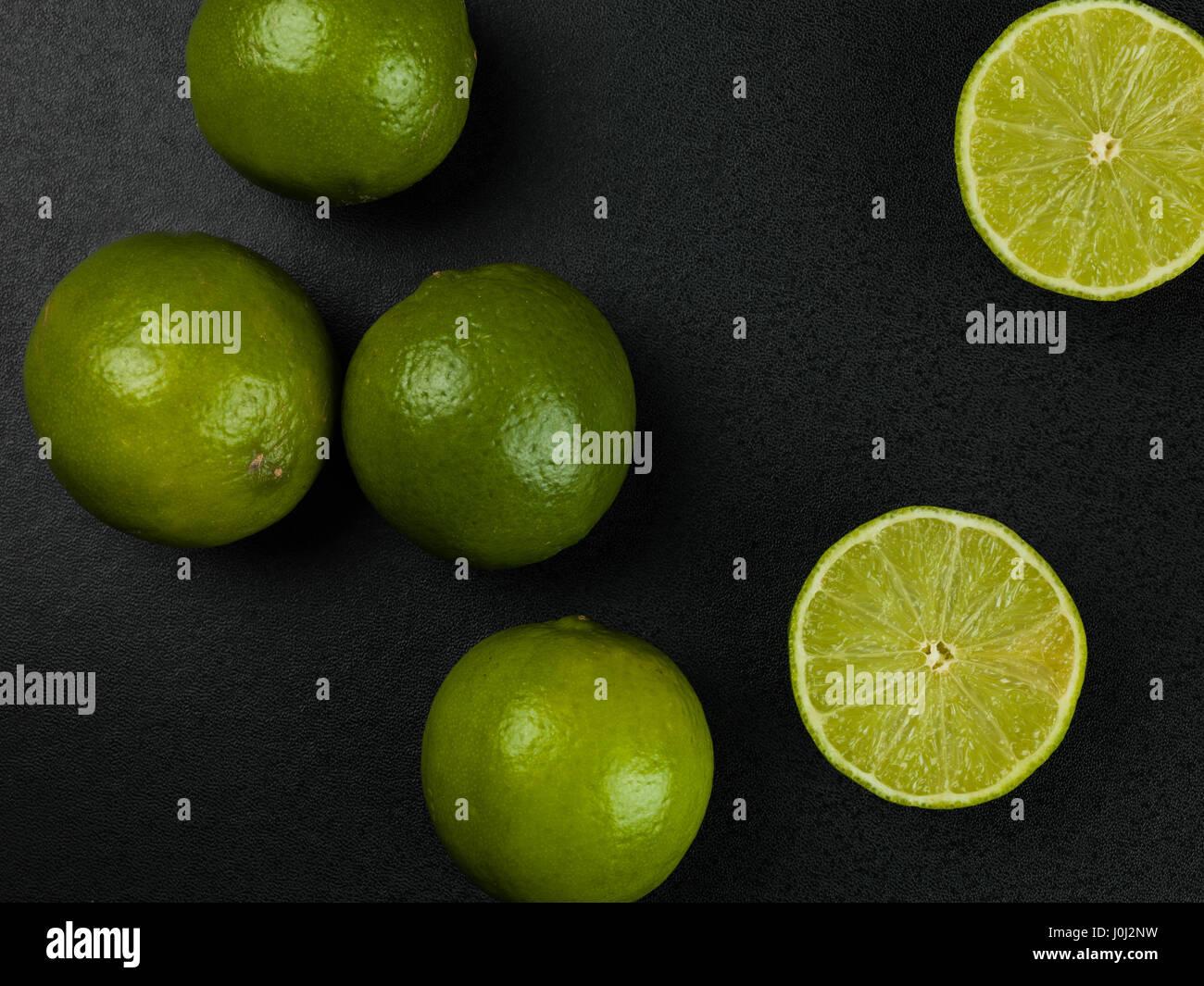 Fresh Ripe Juicy Limes Citrus Fruit Against a Black Background - Stock Image