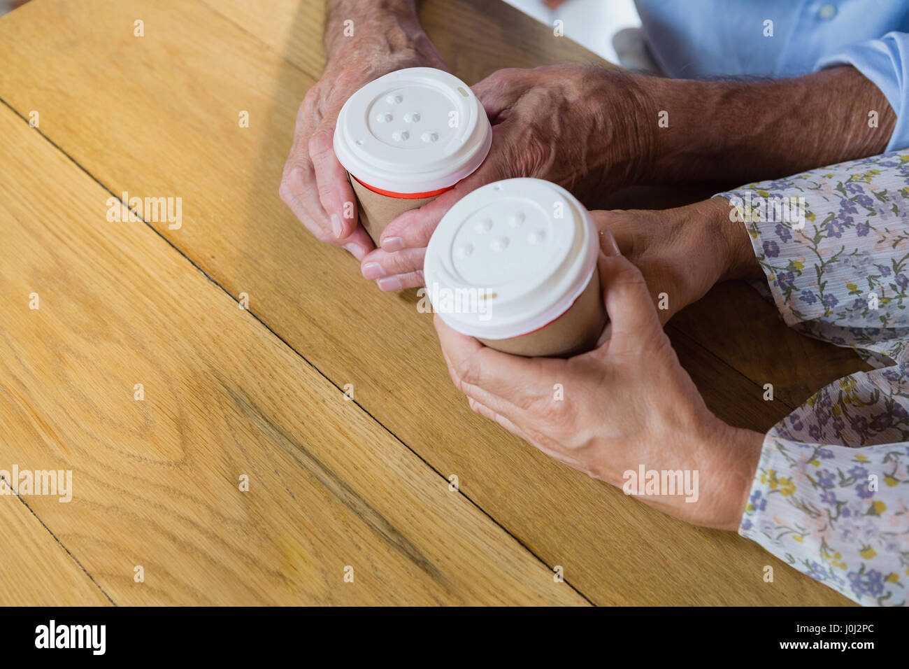 Senior couple holding disposable coffee cup in café - Stock Image