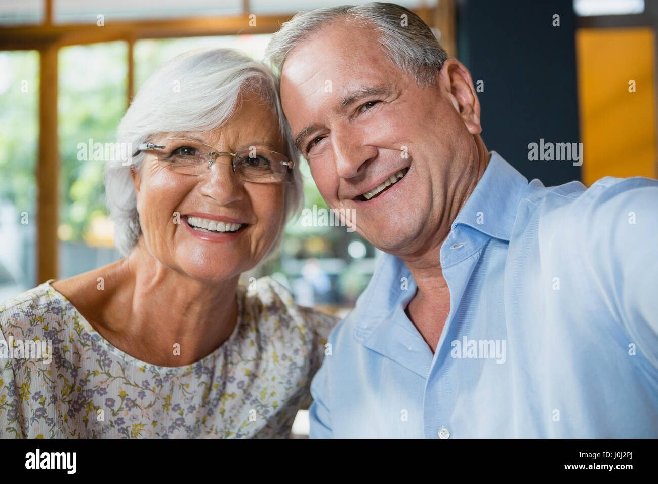 Portrait of happy senior couple sitting in café Stock Photo