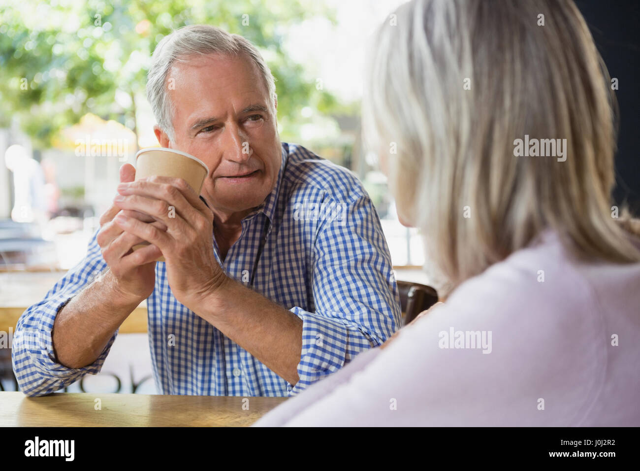 Senior couple interacting with each other in café - Stock Image