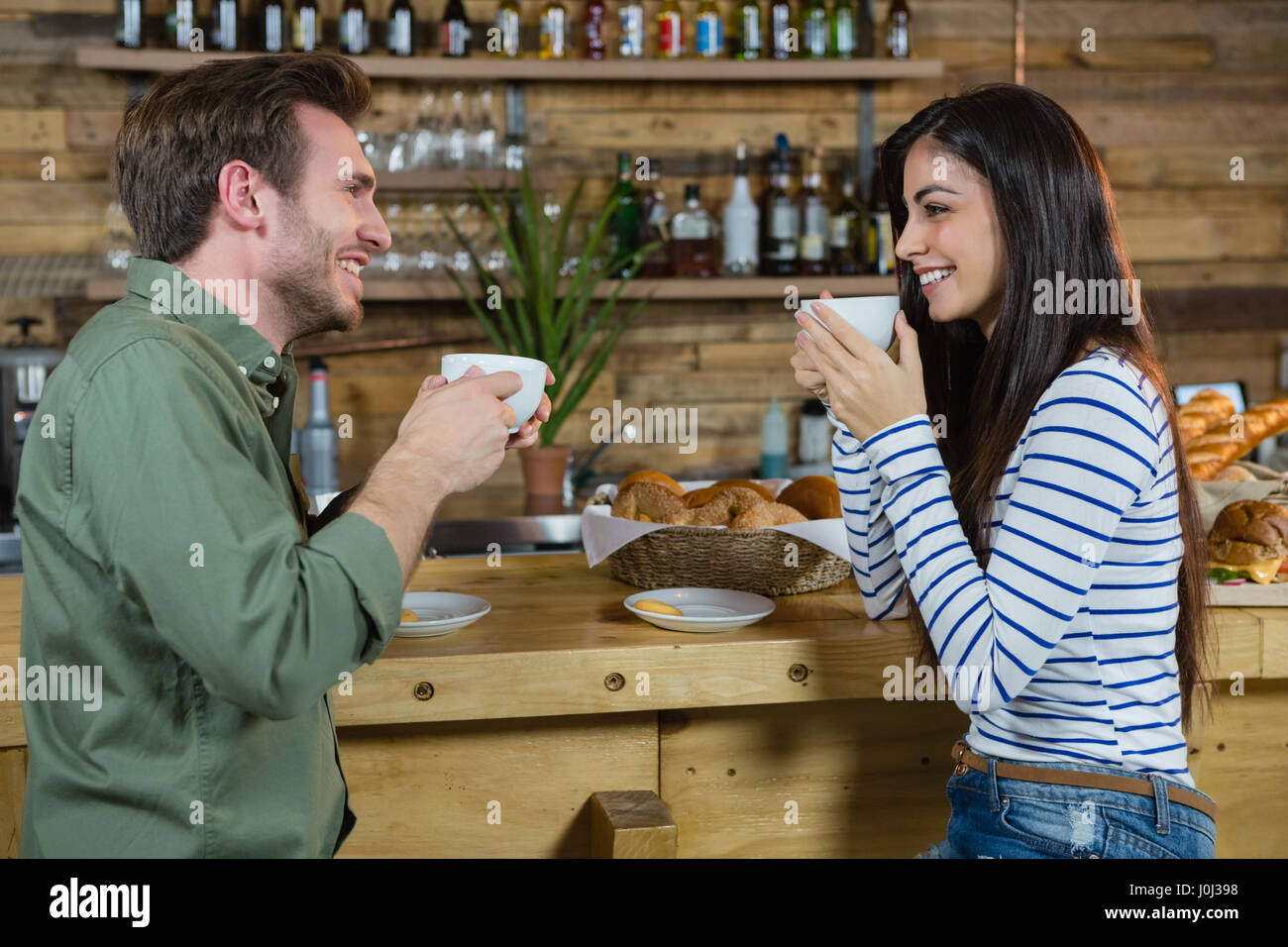 Couple interacting each other while having coffee at counter in café Stock Photo