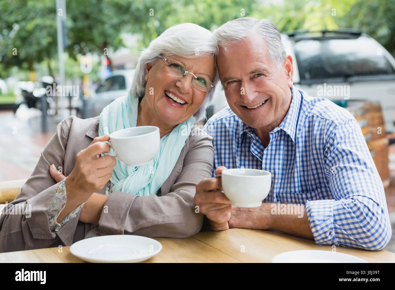 Portrait of senior couple having coffee in outdoor café - Stock Image