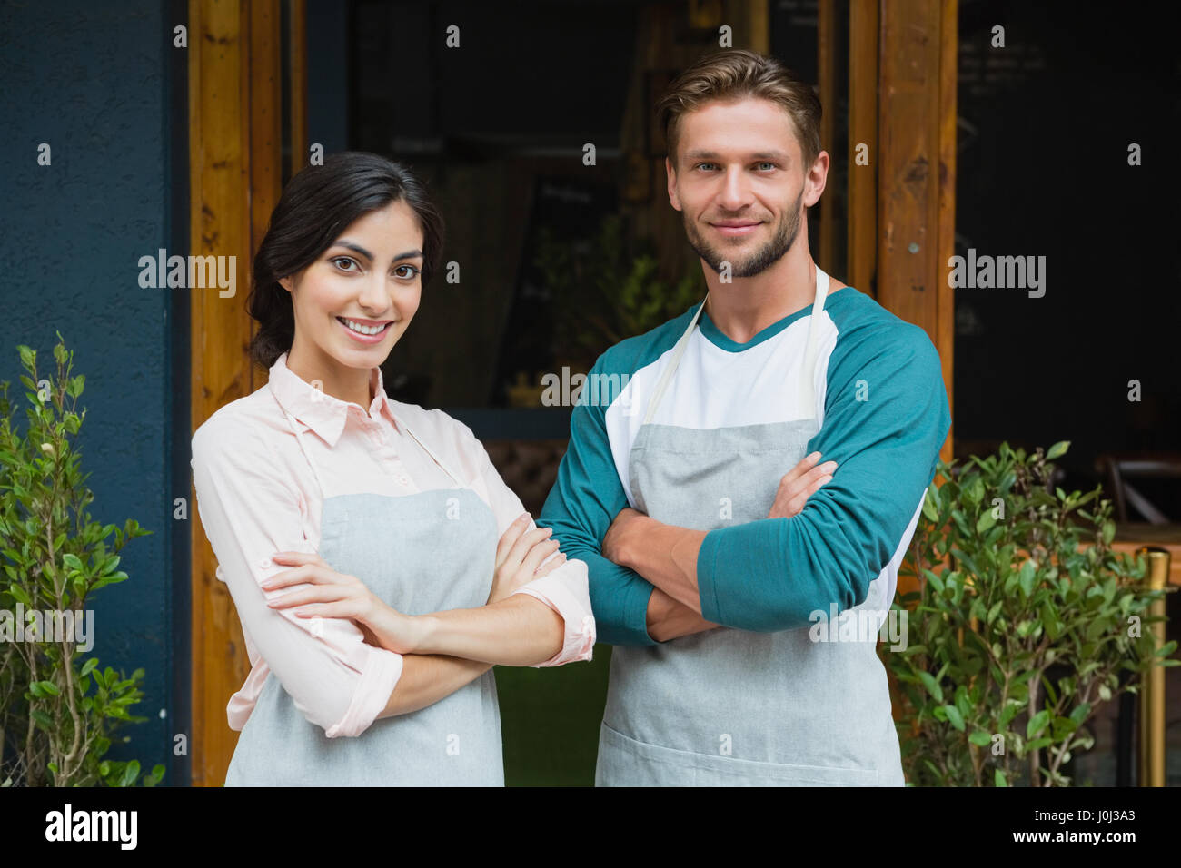 Portrait of smiling waiter and waitress standing with arms crossed outside the cafe - Stock Image