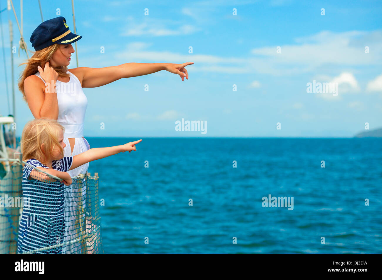 Happy family aboard. Mother in captain cap, little daughter on board of sailing yacht. Children have fun discovering - Stock Image