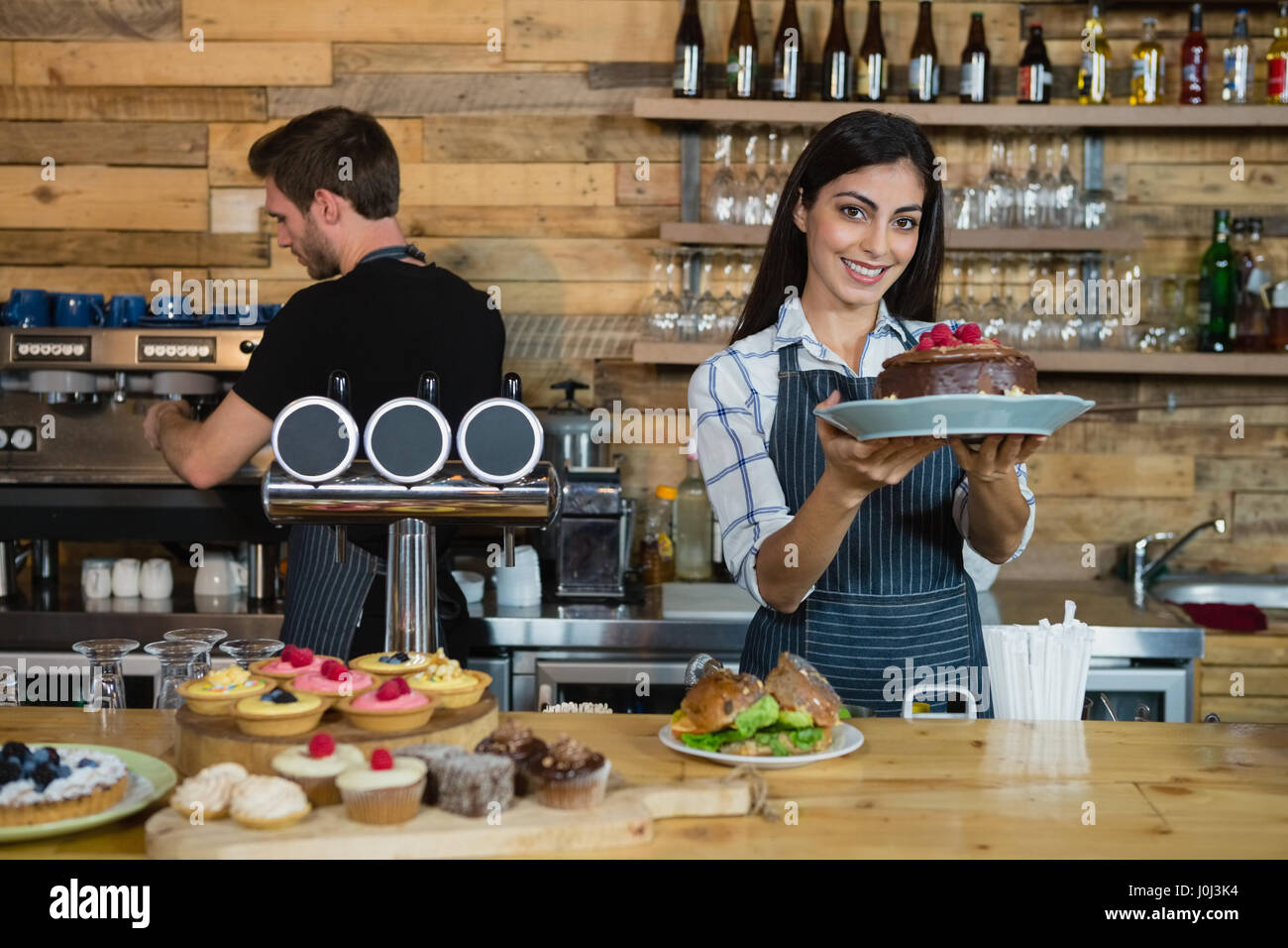 Portrait of smiling waitress holding a chocolate cake at counter in café Stock Photo