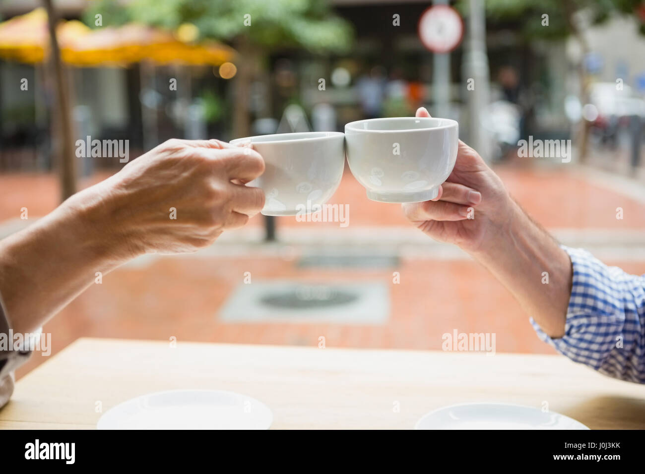 Hands of senior couple toasting coffee cups in outdoor cafe - Stock Image