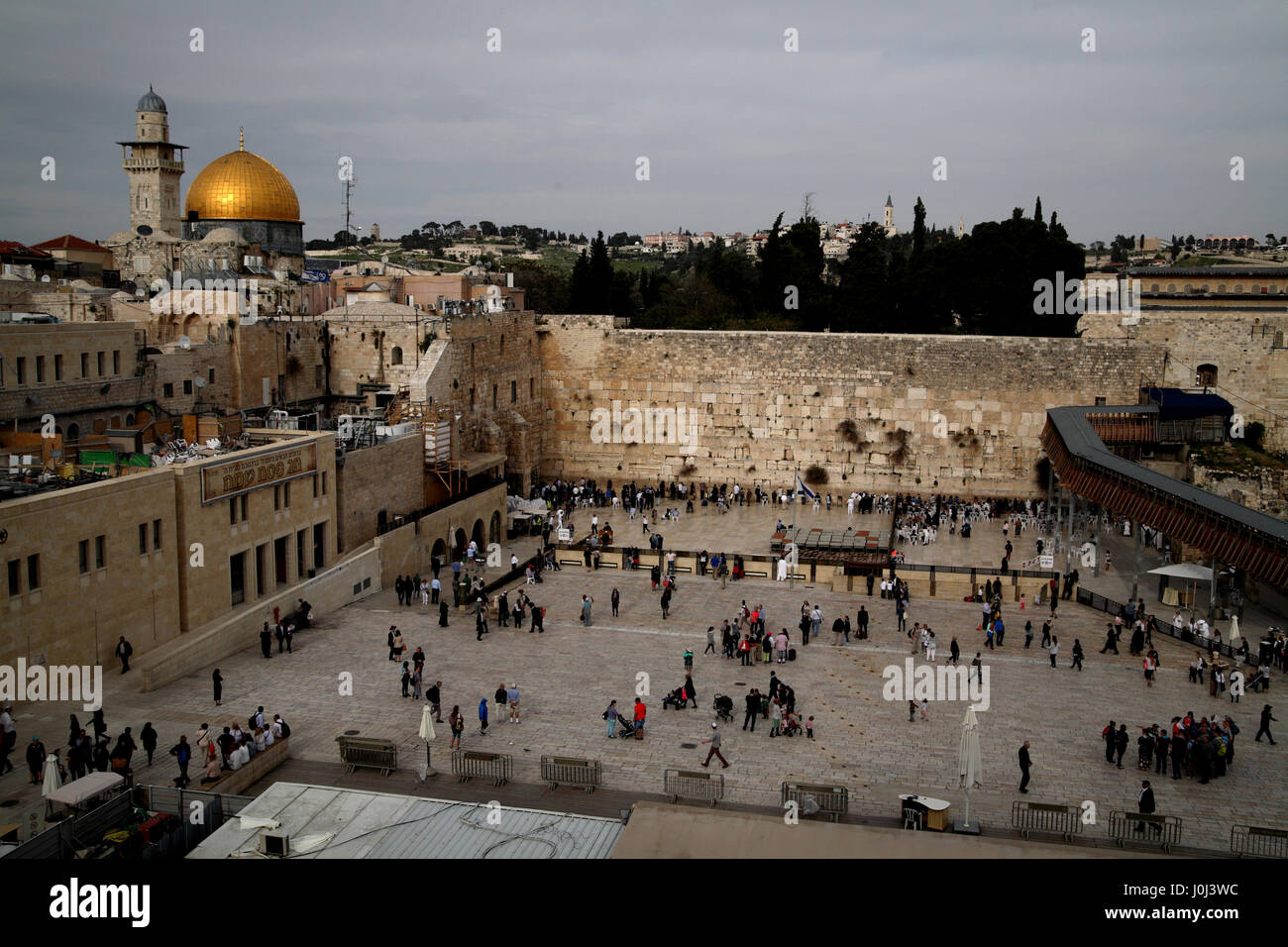 The Wailing wall with Jews attending it for prayer and above it on the left the golden Dome of the Rock on the Termple - Stock Image