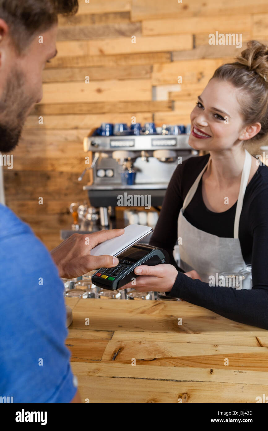 Smiling woman holding credit card reader machine at cafe shop - Stock Image
