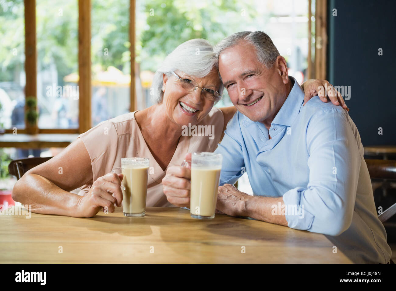 Portrait of happy senior couple having cold coffee in café - Stock Image