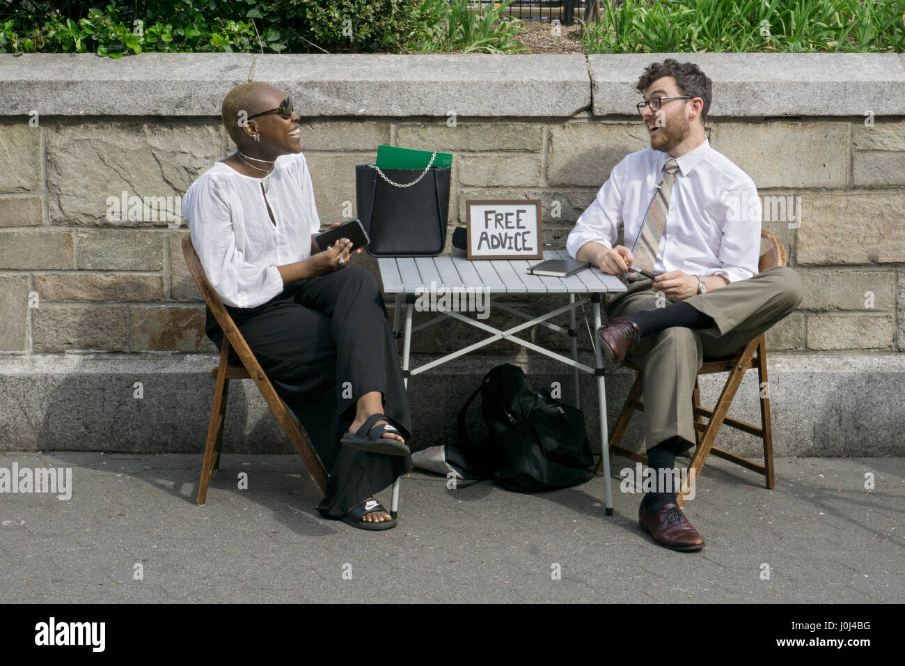 A young man giving free advice to a woman in Union Square Park in Manhattan, New York City. - Stock Image