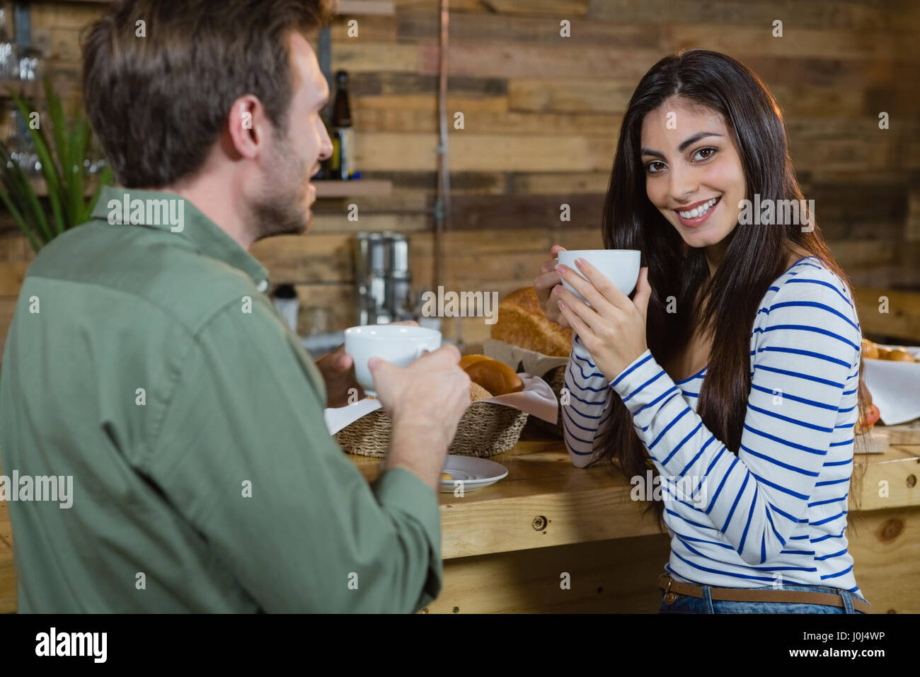 Portrait of woman having coffee at counter in café - Stock Image