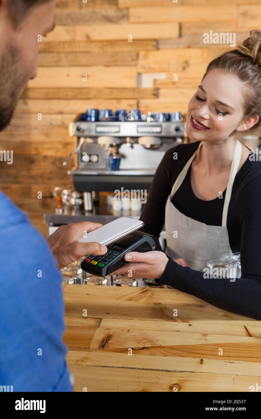 Customer making payment on credit card reader machine at cafe shop - Stock Image