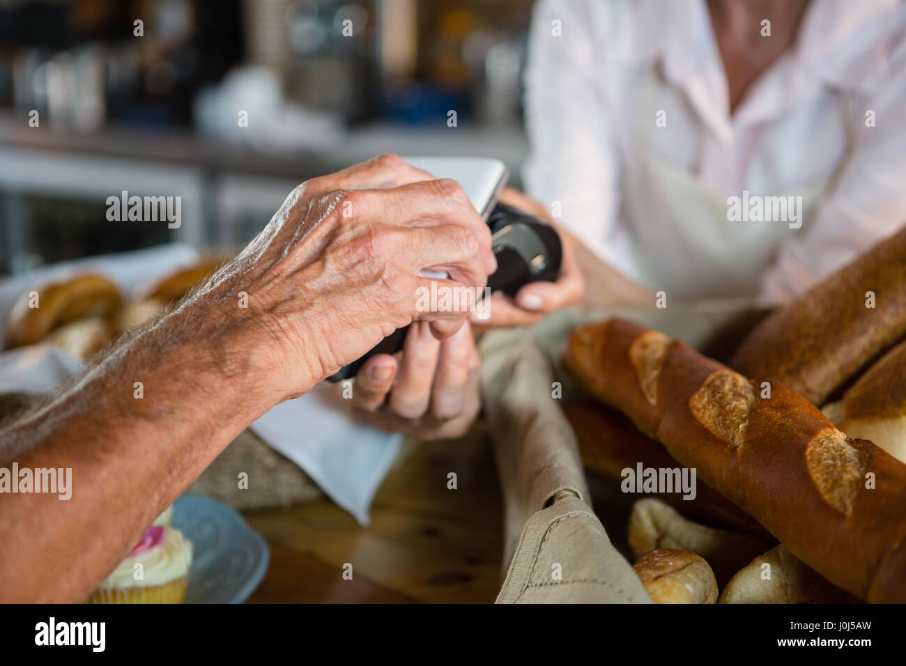 Customer making payment through NFC technology on mobile phone in café - Stock Image