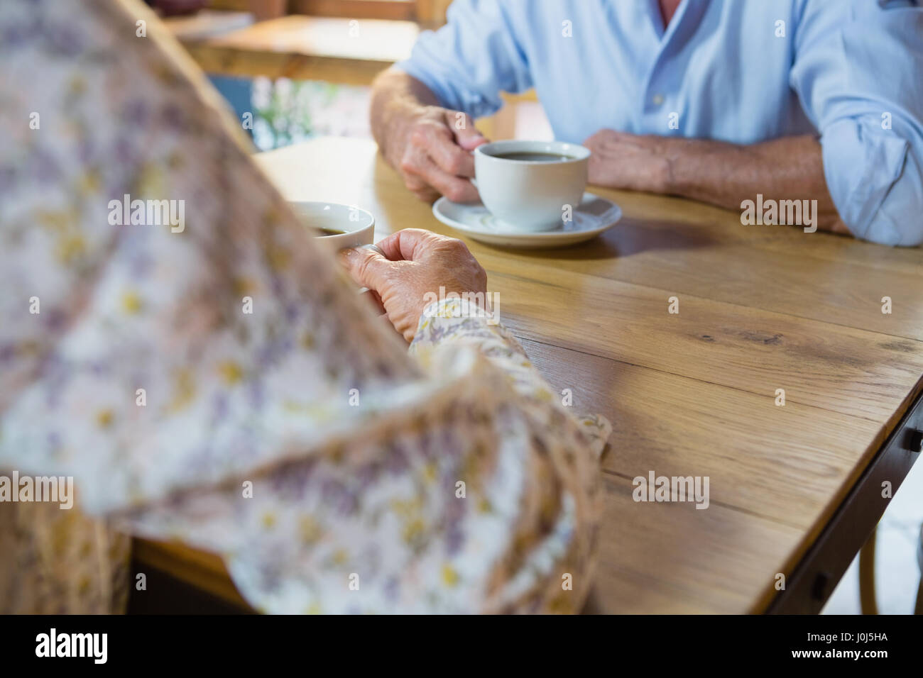 Mid section of senior couple having coffee in café - Stock Image