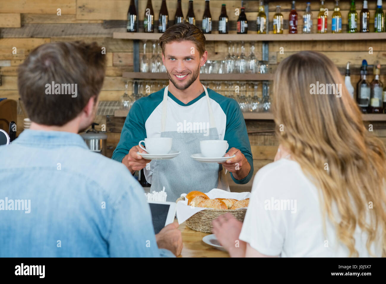 Smiling waiter serving cup of coffee to customers at counter in cafe - Stock Image
