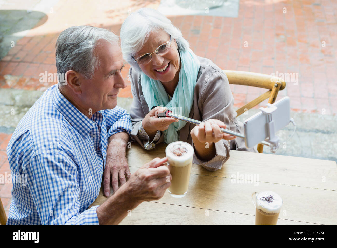 Senior couple taking selfie from mobile phone in outdoor café Stock Photo