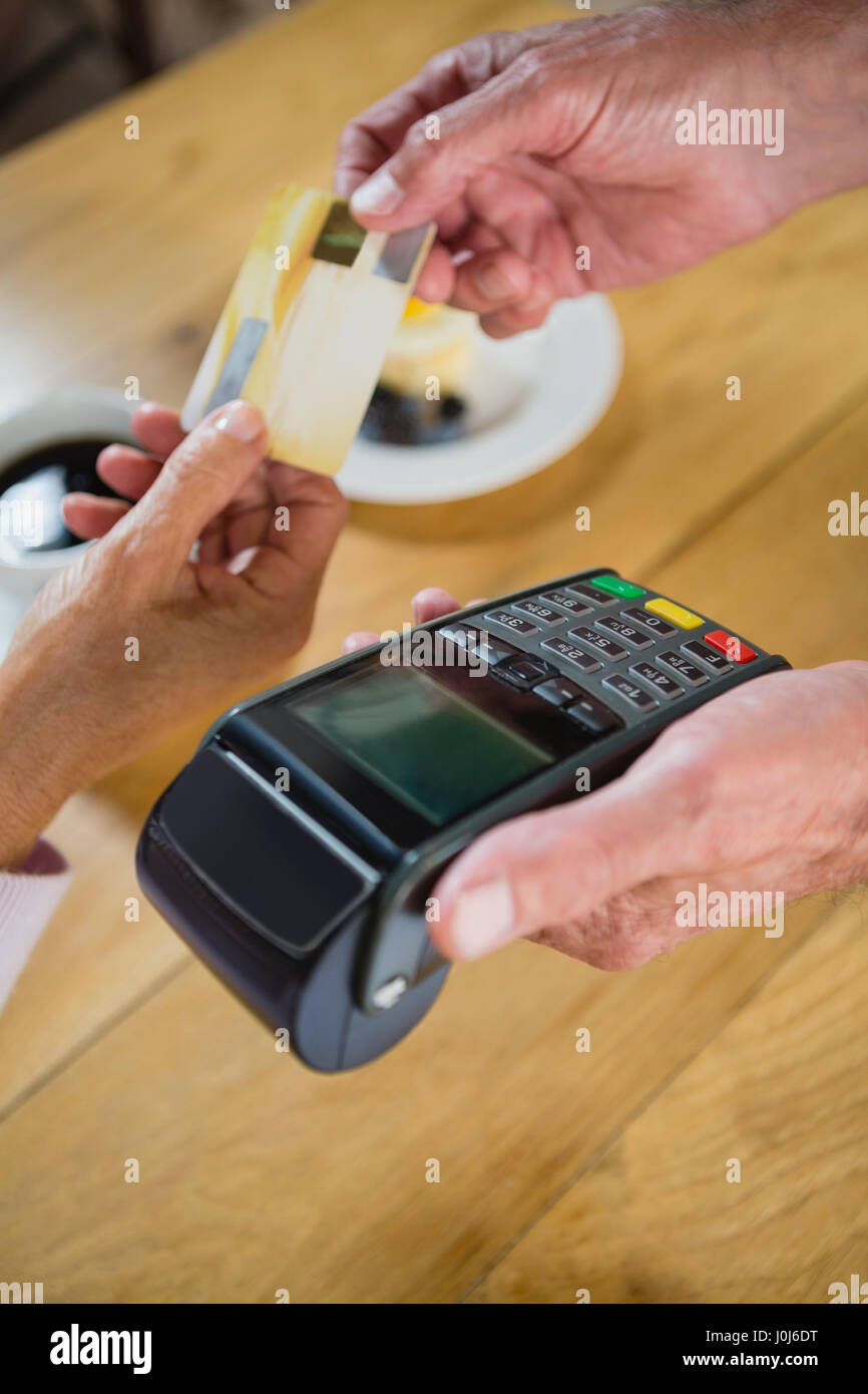 Senior woman making payment through credit card in café - Stock Image