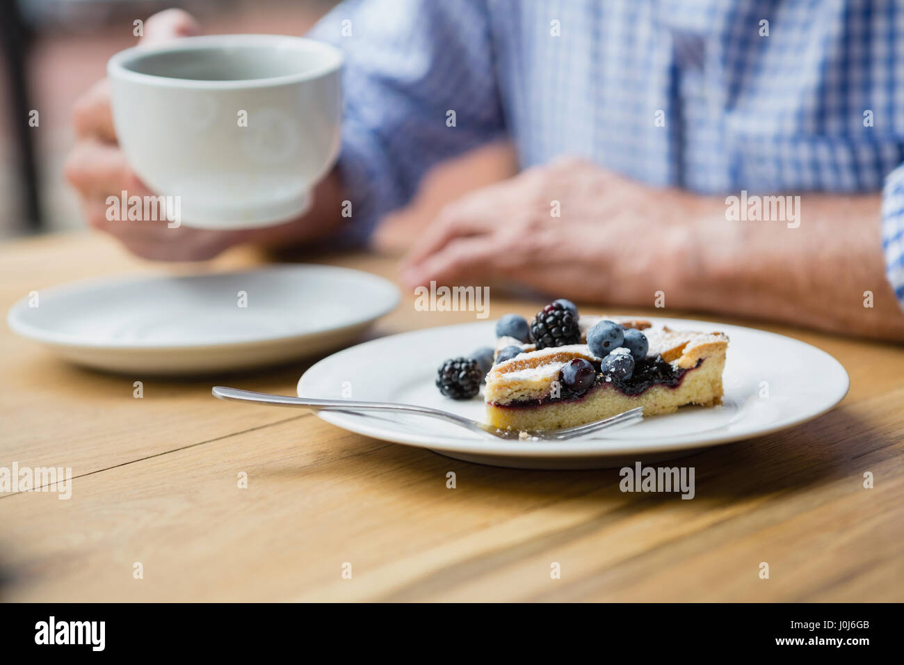 Mid-section of senior man holding a coffee cup in cafe - Stock Image