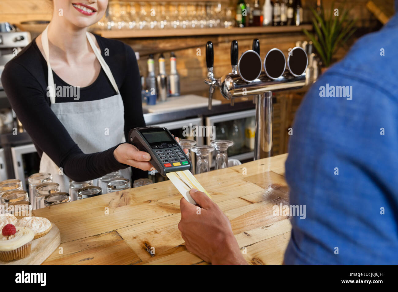 Man making payment on credit card reader machine at cafe shop - Stock Image