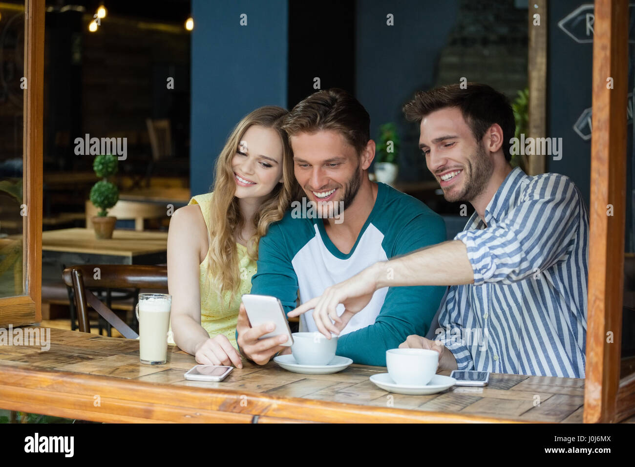 Happy friends looking at smart phone while sitting by table in cafe shop - Stock Image