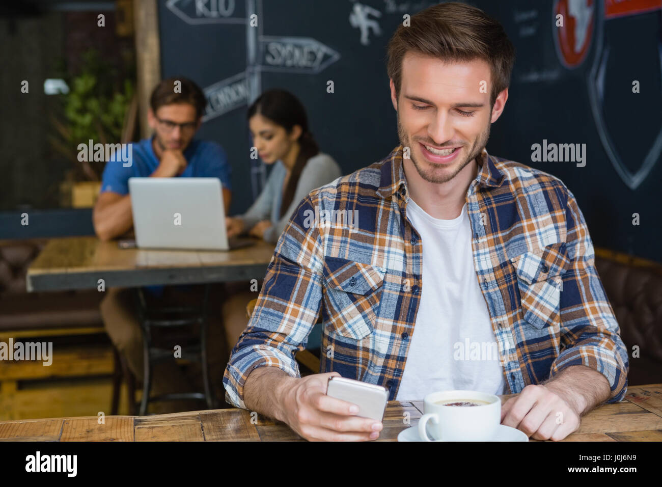Man using mobile phone while having coffee in café - Stock Image