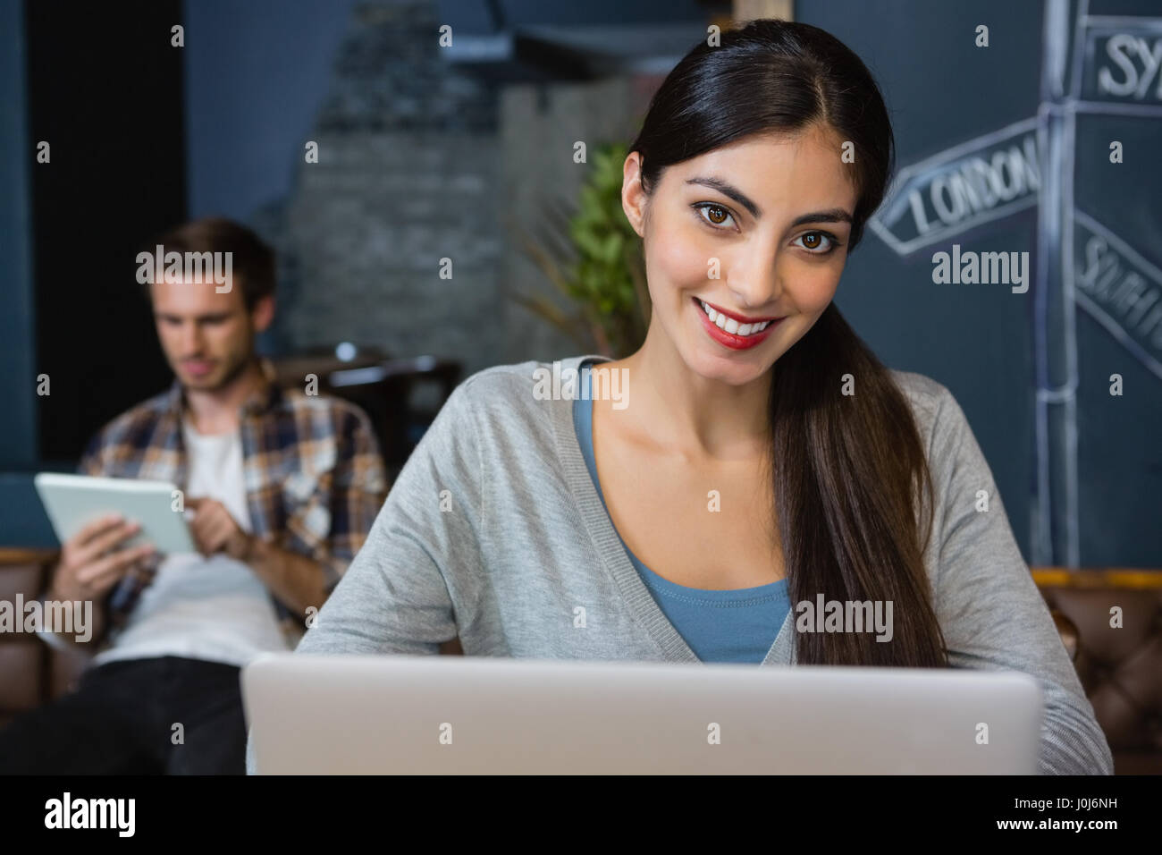 Portrait of young woman using laptop in café - Stock Image